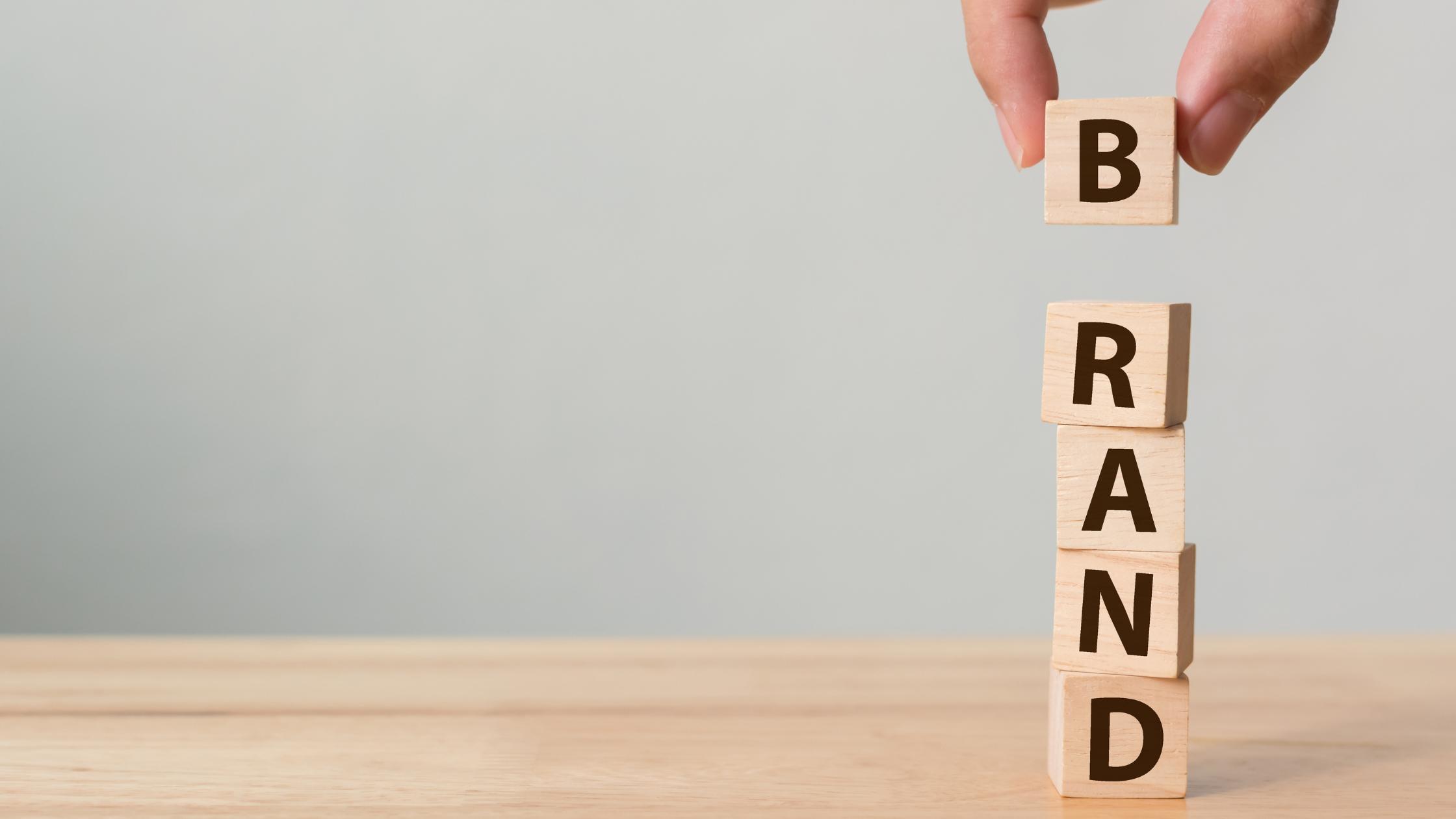 immagine che rappresenta dei cubetti in legno con scritte rispettivamente le lettere della parola Brand e una mano che tiene la lettera B